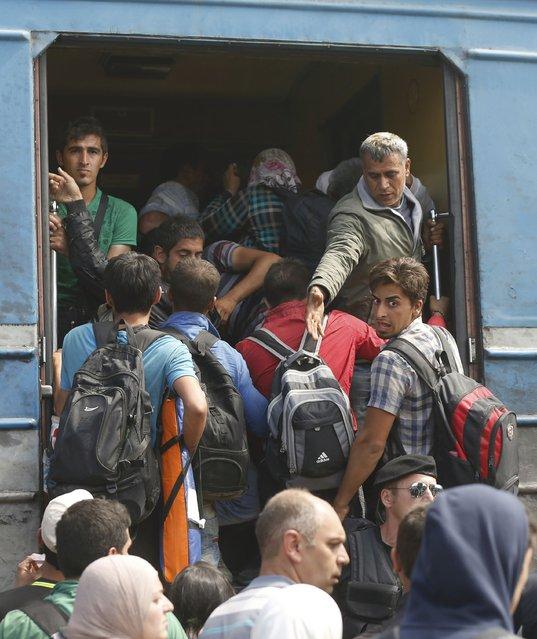 Migrants board a train near Gevgelija, Macedonia, September 7, 2015. (Photo by Stoyan Nenov/Reuters)