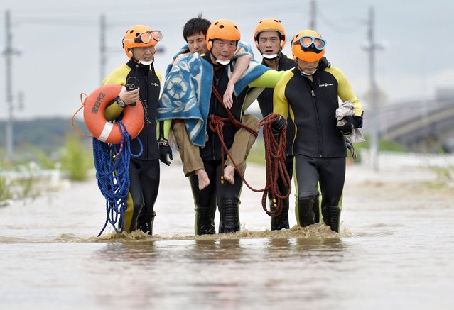 A man (2nd L) is rescued by firefighters at an area flooded by the Kinugawa river, caused by typhoon Etau in Joso, Ibaraki prefecture, Japan, in this photo taken by Kyodo September 10, 2015. (Photo by Reuters/Kyodo News)