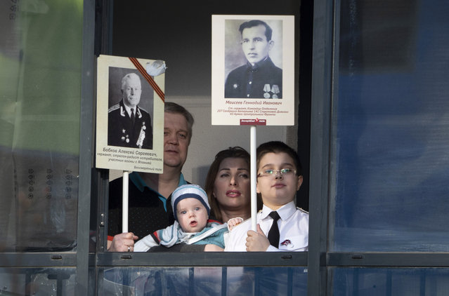 Ermakov's family who cannot go outside to celebrate Victory Day due to coronavirus hold portraits of their ancestors, participants in World War II while standing on the balcony of their apartment in St. Petersburg, Russia, Saturday, May 9, 2020. Victory Day, the anniversary of the defeat of Nazi Germany in World War II, is Russia's most important secular holiday and this year's observance had been expected to be especially large because it is the 75th anniversary, but military parades in Russian cities and a mass processions called The Immortal Regiment were postponed as part of measures to stifle the spread of the virus. (Photo by Dmitri Lovetsky/AP Photo)