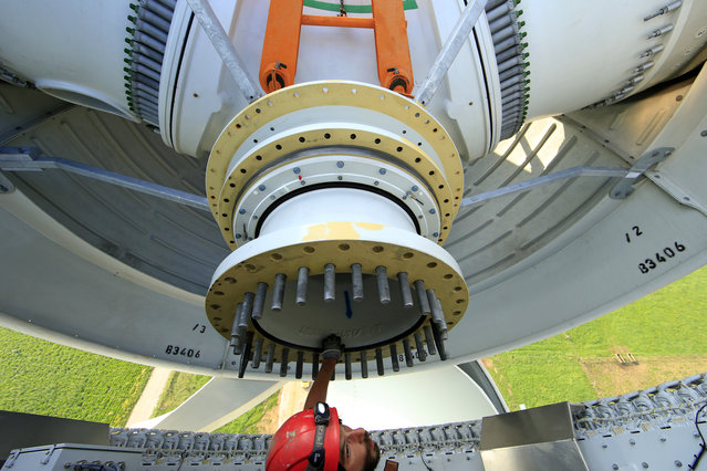 A worker installed in the nacelle part controls the assembling of the rotor hub of a wind turbine in Meneslies, France July 23, 2014. (Photo by Benoit Tessier/Reuters)