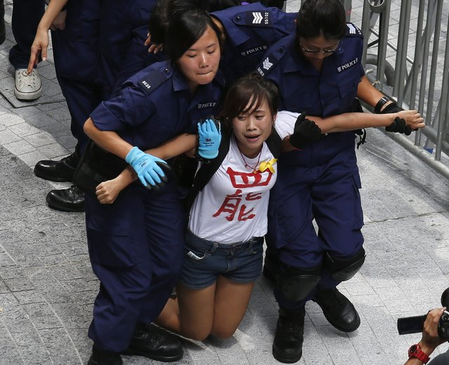 """A protester reacts as she is dragged away by police after storming in government headquarters in Hong Kong September 27, 2014. Hong Kong riot police used pepper spray to disperse protesters around government headquarters on Saturday, fuelling tension ahead of a planned sit-in by pro-democracy activists to protest against Beijing's tightening grip on the city. The word on the T-shirt reads, """"Boycott"""". (Photo by Bobby Yip/Reuters)"""