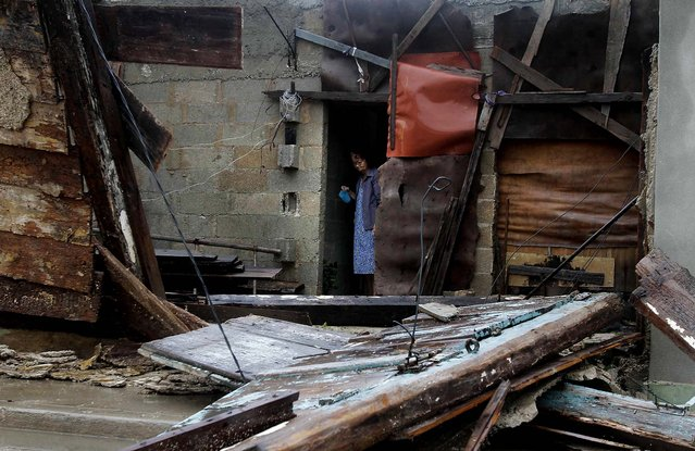 A woman peers from the doorway of her cement home that is being built within the frame of a wooden home, which was partially knocked down as Hurricane Sandy passed through Gibara, Cuba. (Photo by Franklin Reyes/Associated Press)
