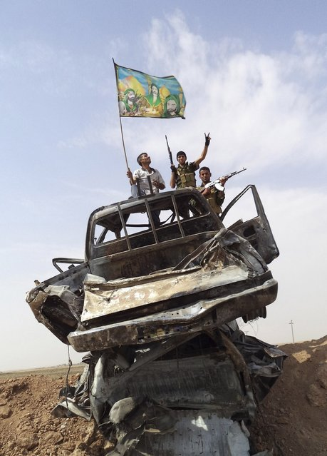 Iraqi Shi'ite militia fighters stand atop destroyed vehicles belonging to Islamic State militants outside Bo Hassan village near Tikrit, northern Iraq October 2, 2014. The flag shows images depicting Shi'ite imams. (Photo by Reuters/Stringer)