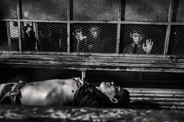 """""""San Pedro Sula"""". Two Children are coming to see the corpse of the Gang killed by suffocation in the prison of San Pedro Sula is taken to the morgue of the Hospital Mario Catarino Rivas. San Pedro Sula, Honduras in August 2014. Photo location: San Pedro Sula, Honduras. (Photo and caption by Javier Arcenillas/National Geographic Photo Contest)"""