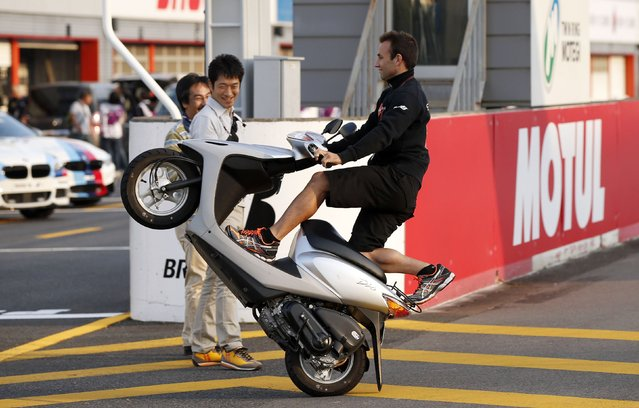 Caterham Suter Moto2 rider Johann Zarco of France performs a wheelie on the track during his course inspection at the Twin Ring Motegi circuit ahead of Sunday's Japanese Grand Prix in Motegi, north of Tokyo October 9, 2014. (Photo by Toru Hanai/Reuters)