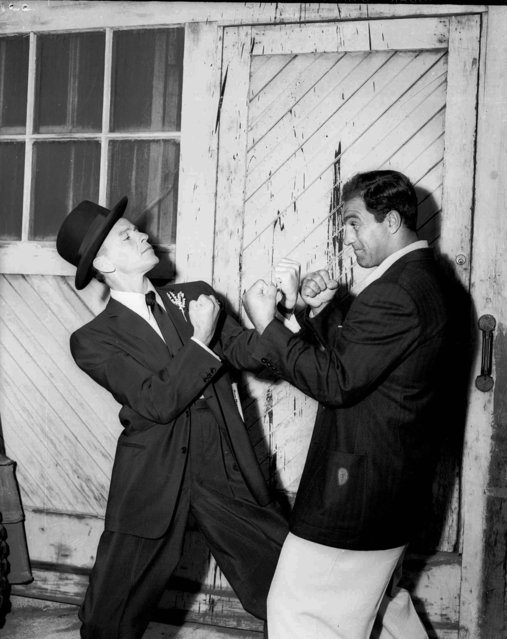 """Frank Sinatra, who fancies himself something of a pugilist, squares off with the world's heavyweight champion, Rocky Marciano, but you can tell from the stance that it's all in fun. The horseplay occurred while Marciano visited the """"Guys and Dolls"""" movie set in Hollywood, May 26, 1955. (Photo by AP Photo)"""