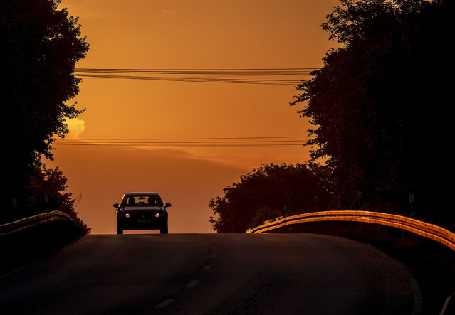 A car comes along a land road in Frankfurt, Germany, as the sun rises Wednesday, May 13, 2020. (Photo by Michael Probst/AP Photo)