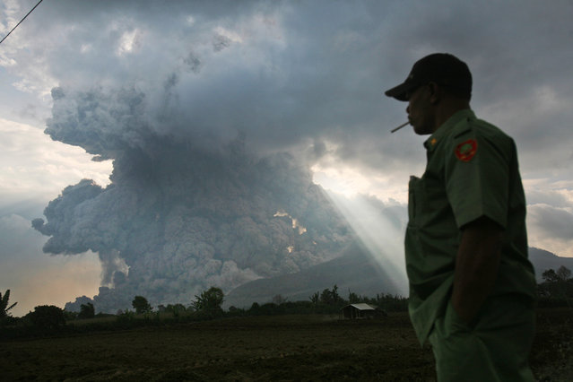 An Indonesian man watches as Mount Sinabung erupts, in Tiga Kicat, North Sumatra, Indonesia, Monday, October 13, 2014. Mount Sinabung, among about 130 active volcanoes in Indonesia, has sporadically erupted since 2010 after being dormant for 400 years. (Photo by Binsar Bakkara/AP Photo)