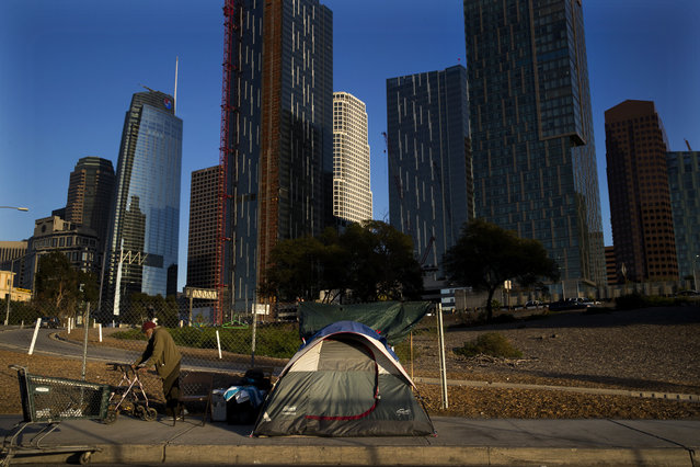 A homeless man, who declined to give his name, is dwarfed by skyscrapers Monday, December 4, 2017, in Los Angeles. The U.S. Department on Housing and Urban Development release of the 2017 homeless numbers are expected to show a dramatic increase in the number of people lacking shelter along the West Coast. (Photo by Jae C. Hong/AP Photo)