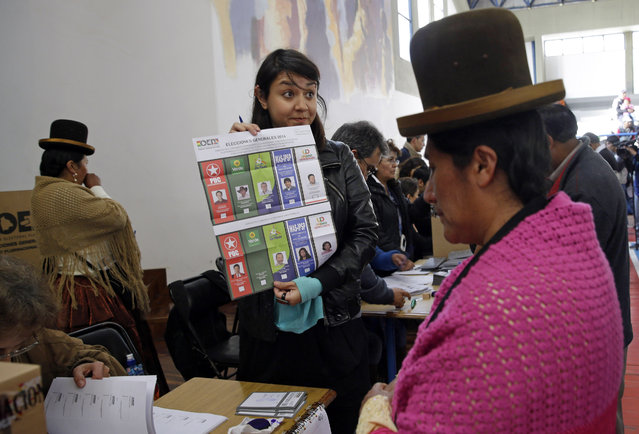 An elections delegate shows an unmarked ballot before giving it to a voter at the polling station in La Paz, Bolivia Sunday October 12, 2014. Bolivia is holding general and presidential elections Sunday with President Evo Morales appearing to be  headed to an unprecedented third term. (Photo by Martin Mejia/AP Photo)