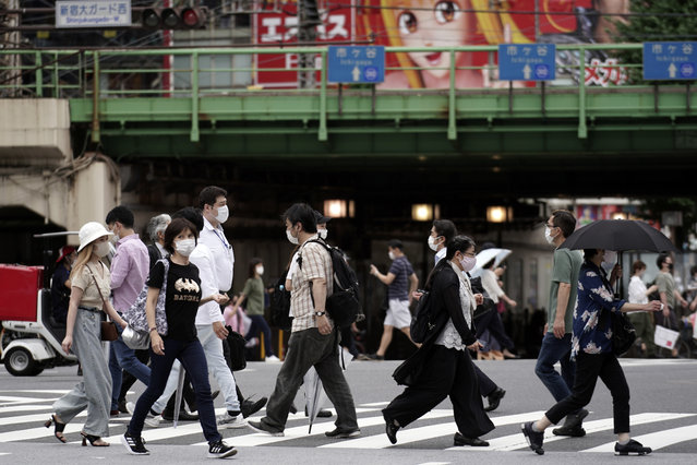 People wearing protective face masks to help curb the spread of the coronavirus walk at a pedestrian crossing Friday, July 10, 2020, in Tokyo. The Japanese capital has confirmed more than 240 new coronavirus infections on Friday, exceeding its previous record. (Photo by Eugene Hoshiko/AP Photo)