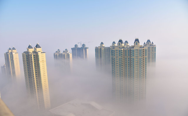 Residential buildings are seen among fog in Songyuan, Jilin province, China April 1, 2017. (Photo by Reuters/Stringer)