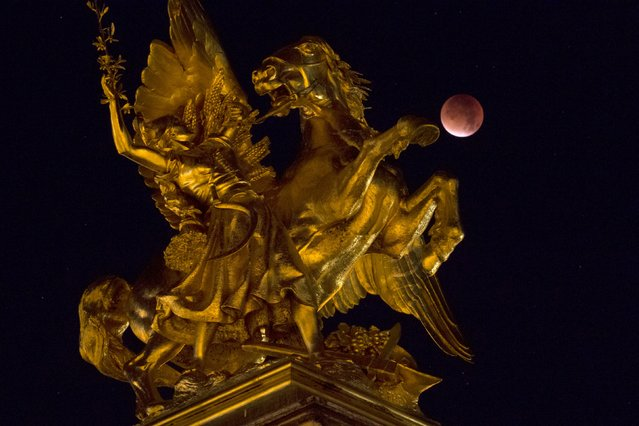 The Moon, appearing next to a statue on the Alexander III bridge, in a dim red colour, is covered by the Earth's shadow during a total lunar eclipse over Paris, France September 28, 2015. Sky-watchers around the world were treated when the shadow of Earth cast a reddish glow on the moon, the result of rare combination of an eclipse with the closest full moon of the year. (Photo by Philippe Wojazer/Reuters)