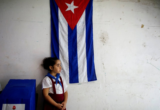 Sofia Ema, 8, waits for voters at a polling station in Havana, Cuba on November 26, 2017. (Photo by Alexandre Meneghini/Reuters)