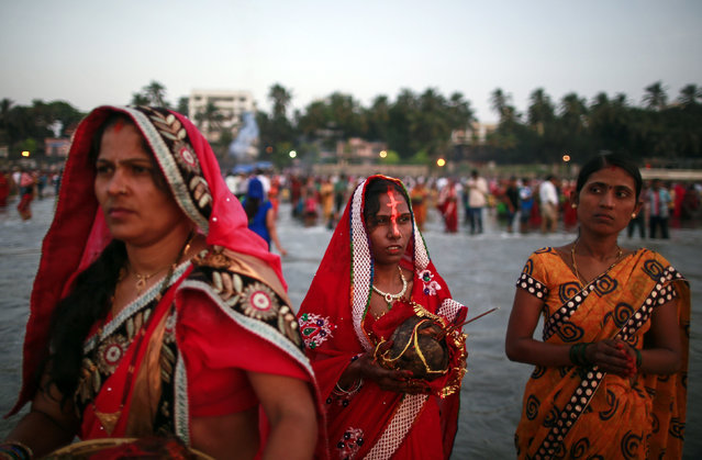 Hindu devotees pray while standing in the waters of the Arabian Sea as they worship the Sun god Surya during the Hindu religious festival Chatt Puja in Mumbai October 29, 2014. (Photo by Danish Siddiqui/Reuters)