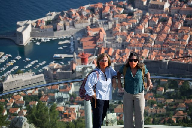 Tourists with protective masks stay on cable car upper station above the old town of Dubrovnik, Croatia, on July  13, 2020, as the country faces shortage of tourists amid the crisis linked with the Covid-19 pandemic caused by the novel coronavirus. (Photo by Ivan Vukovic/AFP Photo)