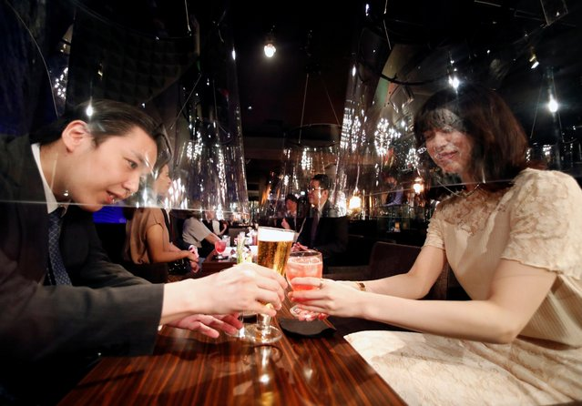Goldfish bowl-like acrylic screens used as part of new social distancing measures, where male customers sit inside the screens to be entertained by female staff, are installed at Jazz Lounge Encounter, a form of night club for seeking encounters, at Ginza district in Tokyo, Japan on August 6, 2020. (Photo by Issei Kato/Reuters)