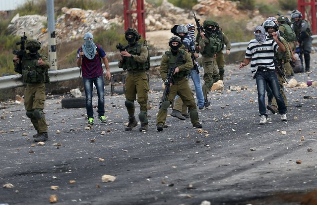 Undercover Israeli security personnel and Israeli soldiers take position during clashes with Palestinians near the Jewish settlement of Bet El, near the West Bank city of Ramallah October 7, 2015. (Photo by Mohamad Torokman/Reuters)