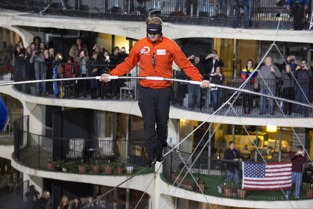 This photo provided by Discovery Communication shows Nik Wallenda walking across the Chicago skyline blindfolded for Discovery Channel's Skyscraper Live with Nik Wallenda on Sunday, November 2, 2014. (Photo by Jean-Marc Giboux/AP Photo/Discovery Communication)