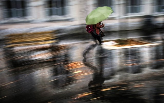 A person walks under the rain with an umbrella in Lyon on November 4, 2014. Some 6,500 homes were left without power in the Ardeche department, south of Lyon, after heavy rains and strong winds raged through the area, which has been placed on orange alert (the second highest weather warning) along with 14 other departments in the south-east. (Photo by Jeff Pachoud/AFP Photo)