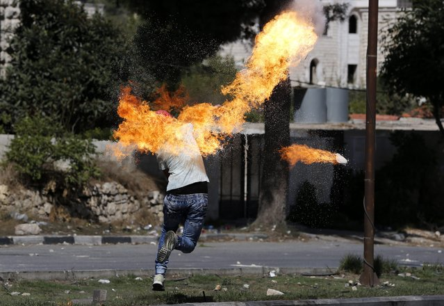 A Palestinian protester sets fire to himself as he throws a molotov cocktail during clashes with the members of the Israeli armed forces in the West Bank city of Hebron, 13 October 2015. The past 12 days have seen the worst spell of street violence in Israel and the Palestinian areas in years, stirred in part by Muslim anger over perceived changes to the status quo observed at a disputed Jerusalem holy site. (Photo by Abed Al Hashlamoun/EPA)