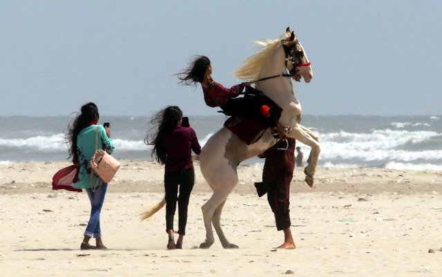 An Afghan girl rides a horse at the beach in Karachi, Pakistan, 07 September 2020. (Photo by Rehan Khan/EPA/EFE)