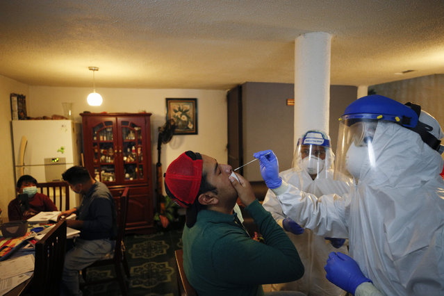 Dr. Ivan Mandujano, right, and nurse Alejandro Ramirez, conduct COVID-19 testing on seven members of the Moreno family, in their home in the Xochimilco borough of Mexico City, Thursday, September 24, 2020. (Photo by Rebecca Blackwell/AP Photo)