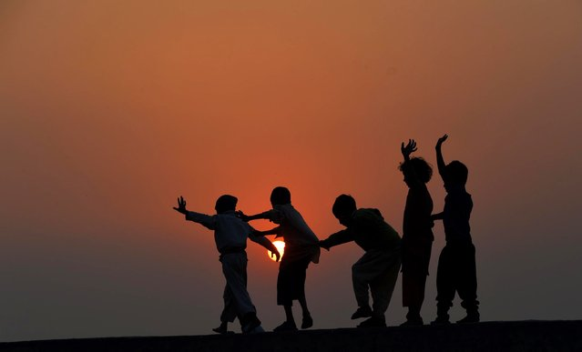 Pakistani children play on the roof of a house on the outskirts of Lahore on November 19, 2014. The United Nations' Universal Children's Day is celebrated annually on November 20 to promote worldwide fraternity and understanding between children. (Photo by Arif Ali/AFP Photo)