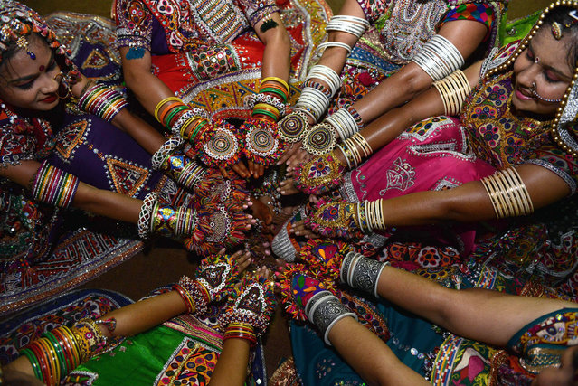 Indian folk dancers display ornaments during a break while participating in the first night of Navratri in Gandhinagar, some 30 km from Ahmedabad, on October 13, 2015. Navratri festivities, or Dance Festival of Nine Nights, takes place between October 13-21. (Photo by Sam Panthaky/AFP Photo)