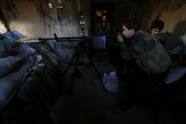 Fighters from the Noureddine Zanki movement, which operates under the Free Syrian Army, take positions as one of them aims his weapon at the frontline against forces loyal to Syria's President Bashar al-Assad in Aleppo's al-Rashideen neighbourhood November 27, 2014. (Photo by Hosam Katan/Reuters)