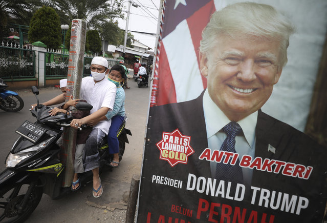 """A man and his sons wearing face masks as a precaution against the coronavirus, ride past an advertisement using a portrait of U.S. President Donald Trump as a gimmick to attract people's attention in Ciputat, Indonesia, Friday, October 2, 2020. President Trump said early Friday that he and first lady Melania have tested positive for the coronavirus, a stunning announcement that plunges the country deeper into uncertainty just a month before the presidential election. Writings on the signboard read: """"Anti-bacterial"""" and """"President Donald Trump has never dropped his laundry here"""". (Photo by Dita Alangkara/AP Photo)"""