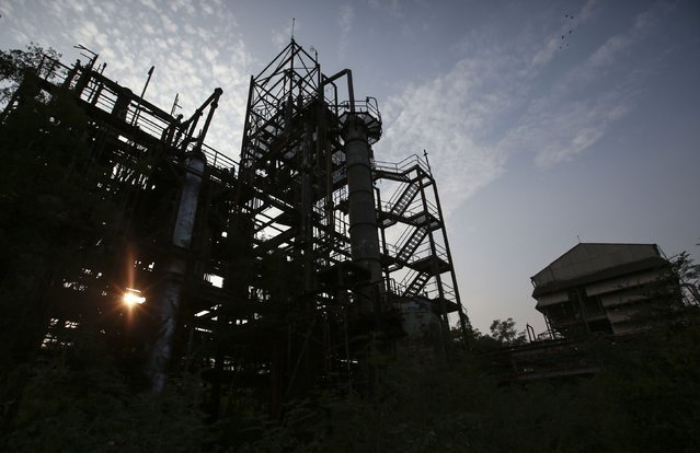 The sun sets behind the abandoned former Union Carbide pesticide plant in Bhopal November 11, 2014. (Photo by Danish Siddiqui/Reuters)