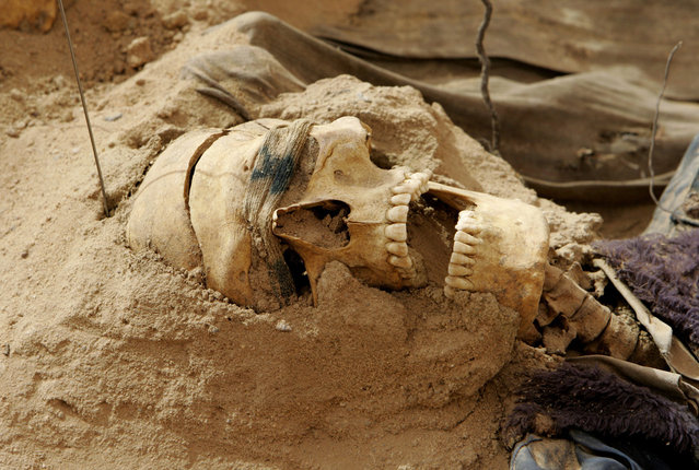 A human skull with blindfold still on lies on a mass grave containing human skeletons and clothes from persons allegedly executed during the regime of former President Saddam Hussein and now unearthed in a shallow grave, in a remote desert south of Baghdad in Iraq, on June 3, 2006. (Photo by Erik de Castro/AP Photo/The Atlantic)