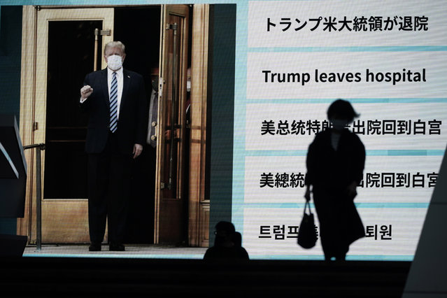 People walk past a screen showing the news report that President Donald Trump has left a hospital to return to the White House after receiving treatments for COVID-19, Tuesday, October 6, 2020, in Tokyo. (Photo by Eugene Hoshiko/AP Photo)