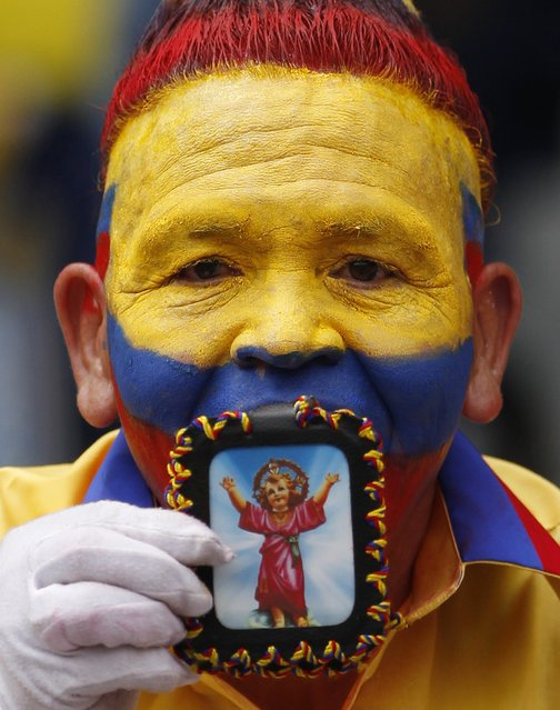 A Colombian fan kisses an image of baby Jesus before the start of a 2014 World Cup qualifying soccer match with Bolivia in Barranquilla, Colombia, Friday, March 22, 2013. (Photo by Fernando Vergara/AP Photo)