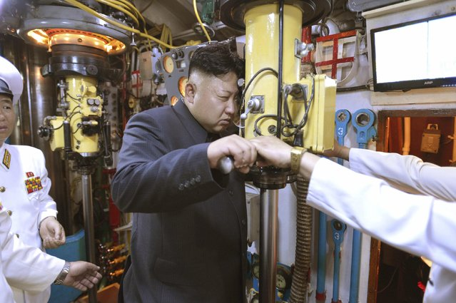 North Korean leader Kim Jong Un (C) looks through a periscope of a submarine during his inspection of the Korean People's Army (KPA) Naval Unit 167, in this undated file photo released by North Korea's Korean Central News Agency (KCNA) in Pyongyang on June 16, 2014. (Photo by Reuters/KCNA)