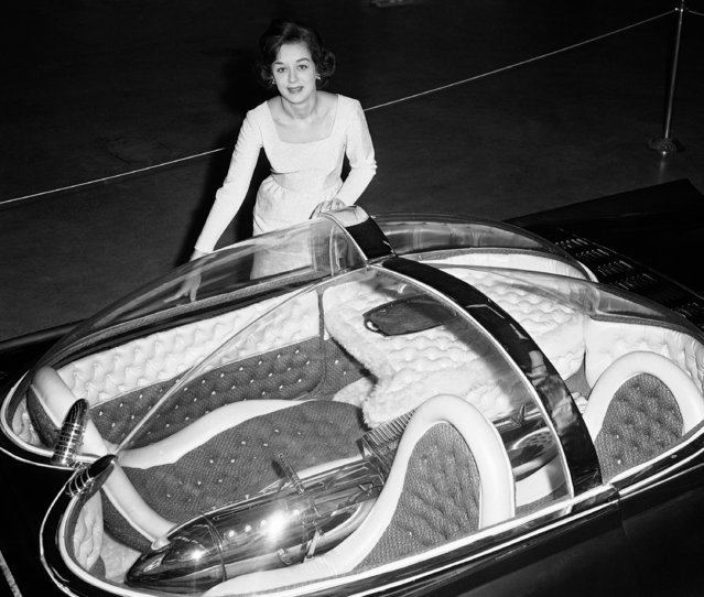 "A mecca for auto buffs is the annual Autorama in Detroit, Michigan, January 10, 1964. This year's show, the 12th, brought out a display of red-hot hot rods and fantastic ""dream cars"", with more conservative custom cars, go-karts, hand-built and antique cars, drag boats and model cars, 250 or more exhibits in all. Cars entered in competition for prizes at the show must have competed successfully in at least four other shows. Palema Dulmage, Queen of the Autorama, stands by space age car. (Photo by Preston Stroup/AP Photo)"