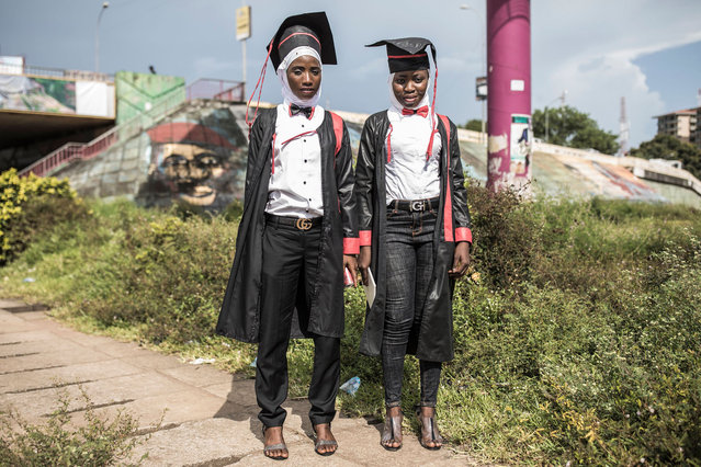 Two young women pose for a portrait, dressed in robes after collecting their Bachelor degrees in Conakry on October 12, 2020. Presidential elections are to be held on October 18, with incumbent President bidding for a third term in office, defying critics who say he forced through a new constitution this year enabling him to sidestep two-term presidential limits. (Photo by John Wessels/AFP Photo)