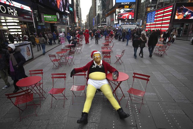 A person dressed up as Homer Simpson sits as he poses for photos in exchange for tips in Times Square on Black Friday in New York November 28, 2014. (Photo by Carlo Allegri/Reuters)