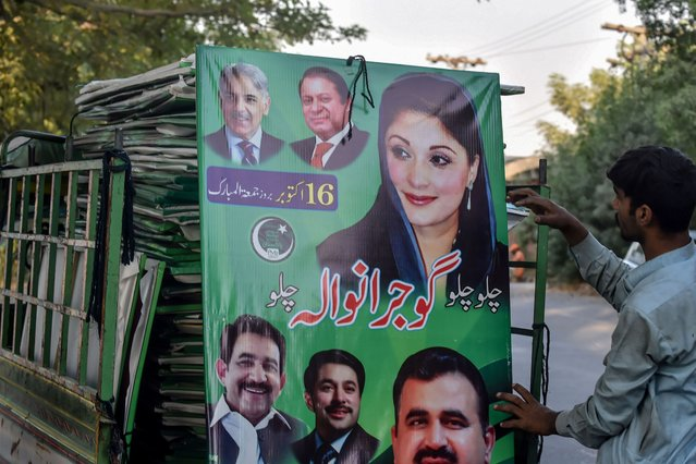 A worker grabs a poster of opposition party Pakistan Muslim League Nawaz (PML-N) to hang it on a street in Lahore on October 15, 2020, as part of preparations ahead of an opposition rally. (Photo by Arif Ali/AFP Photo)