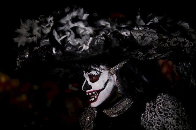 "A man dressed up as a ""Catrina"", a Mexican character also known as ""The Elegant Death"", takes part in a Catrinas parade in Mexico City October 31, 2015. (Photo by Carlos Jasso/Reuters)"