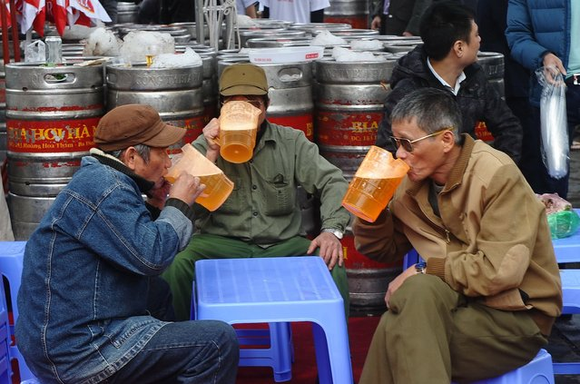 """Men drink beer during a local annual beer festival in Hanoi on December 7, 2014. Thousands of local beer lovers visited the event where they could enjoy for free the popular """"Bia Hoi"""", a local cheap draft beer that is sold on streets of Vietnam's big cities. Some published surveys said Vietnam is top beer-drinking nation among Southeast Asian nations. (Photo by Hoang Dinh Nam/AFP Photo)"""