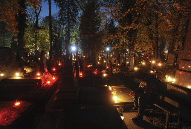 """Ukrainians light candles during the """"Memory Candles for the Lychakiv Cemetery"""" event to celebrate All Saints Day at the Lychakiv Cemetery in Lviv, Ukraine, 01 November 2020. Lychakiv Cemetery is one of the oldest cemeteries in Europe, where many Poles have been buried as Lviv was a Polish city until 1939. (Photo by Mykola Tys/EPA/EFE)"""
