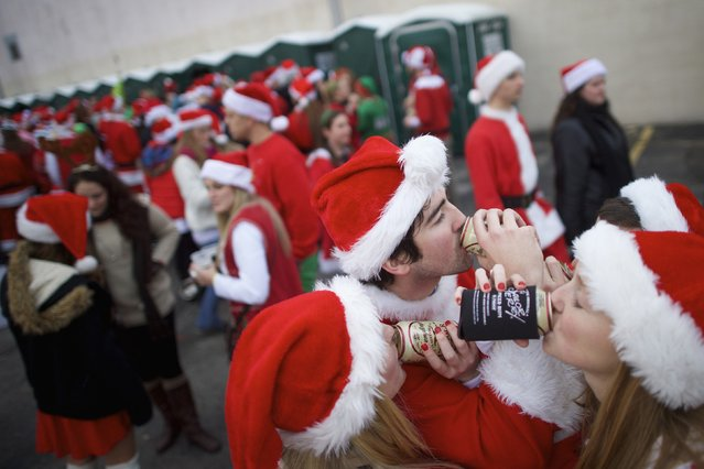 "Drexel University students in Santa Claus outfits (L-R) Megan Miller, 22, and Meredith Lapan, 22, drink beer at an after-party following the ""Running of the Santas"" in Philadelphia, Pennsylvania December 13, 2014. (Photo by Mark Makela/Reuters)"