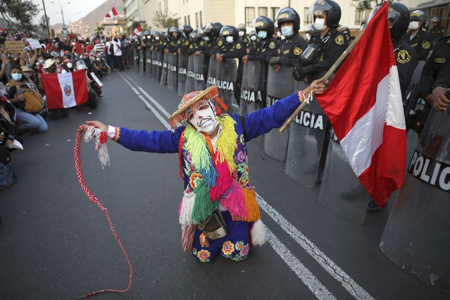 Local folk artists perform next to a police line outside Congress building, as they wait for news from inside on who will be the country's next president, in Lima, Peru, Sunday, November 15, 2020. Interim President Manuel Merino announced his resignation following massive protests unleashed when lawmakers ousted President Martin Vizcarra. (Photo by Rodrigo Abd/AP Photo)