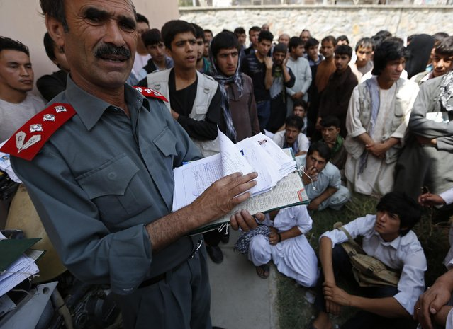 Afghan men wait as an official (L) holds their driving test papers at a traffic police department in Kabul August 23, 2014. (Photo by Mohammad Ismail/Reuters)