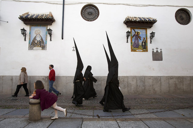 Penitents from the El Nazareno brotherhood walk to the Jesus Nazareno Church as people pass by before a procession during Maundy Wednesday on March 29, 2018 in Cordoba, Spain. Spain celebrates the holy week before Easter with processions in most Spanish towns and villages. (Photo by Pablo Blazquez Dominguez/Getty Images)
