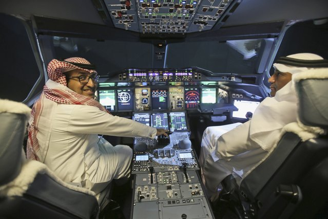 Two visitors of Arab Gulf states visit inside the cockpit of a new Etihad Airways A380 unveiled in an event in Abu Dhabi, United Arab Emirates, Thursday, December 18, 2014. (Photo by Kamran Jebreili/AP Photo)