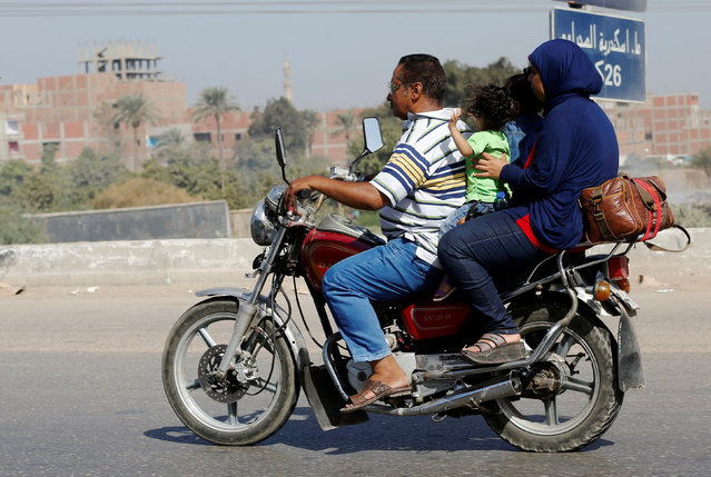A man rides with his family and their belongings on a motorcycle on the agricultural road which leads to the capital city of Cairo, Egypt October 13, 2016. (Photo by Amr Abdallah Dalsh/Reuters)