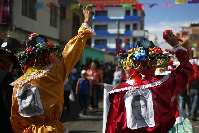 "Ayotzinapa Teacher Training College Raul Isidro Burgos students perform a traditional dance with the pictures of the 43 missing students of September 26, during the ""Paseo del Pendon"", a traditional artistic march in Chilpancingo, December 21, 2014. (Photo by Jorge Dan Lopez/Reuters)"